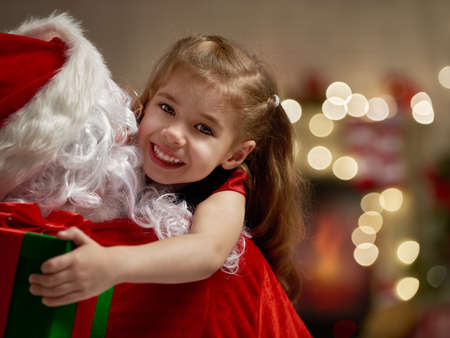 cute little girl smiling: Smiling little girl hugging with Santa Claus.