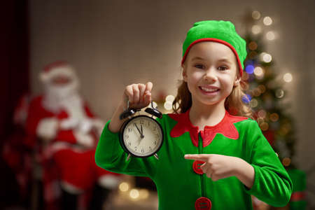 Happy child in Christmas elf costume with alarm.