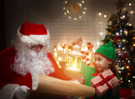 Сute elf helps Santa Claus reading wish list