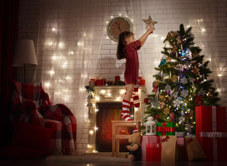 miracle tree: Girl is decorating the Christmas tree Stock Photo