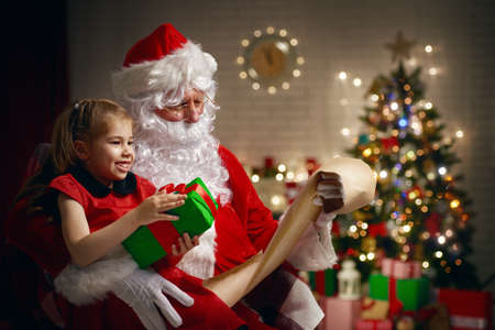 home decoration: Santa Claus giving a present to a little cute girl
