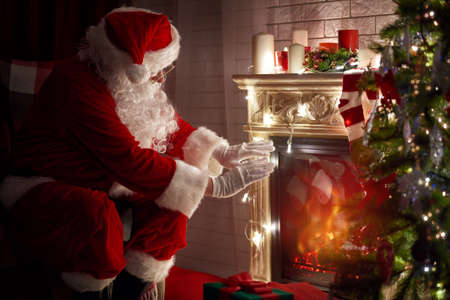 Santa Claus warming his hands at fire fireplace.