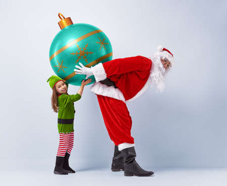 elf: Funny Santa and elf holding together a huge Christmas bauble. Stock Photo