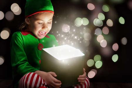 magie: Cute petite fille l'ouverture d'une bo�te de cadeau magique.
