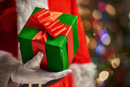 claus: Hands of Santa Claus with Christmas present Stock Photo