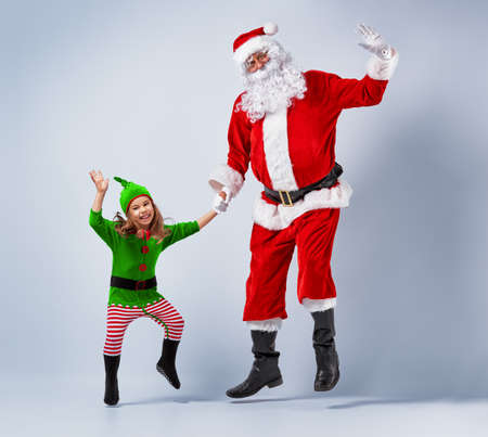 elves: Santa and elf having fun and dancing. Stock Photo
