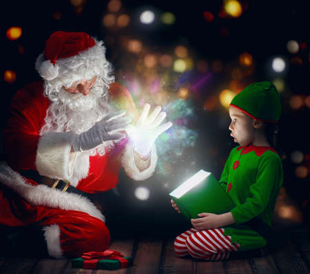 time of the year: Cute little girl and Santa Claus opening a magic gift box. Stock Photo