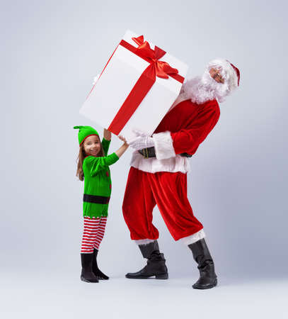 Funny Santa and elf holding together a large Christmas gift.