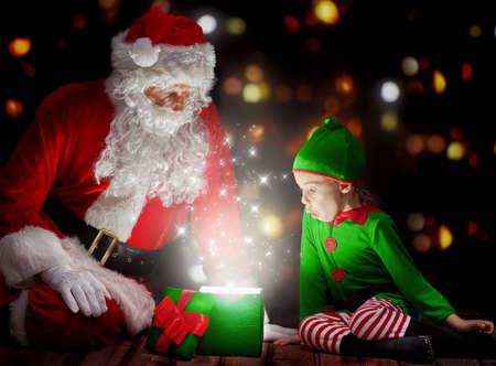 Światła: Cute little girl i Mikołaj otwarcie Magiczne pudełko. Zdjęcie Seryjne