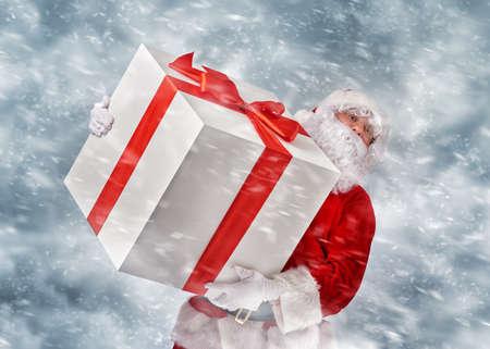 christmas gift box: Santa Claus holding a huge Christmas gift. Stock Photo