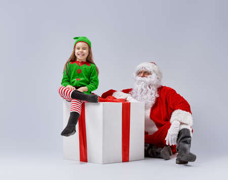 Jolly elf and Santa Claus play together. Stock Photo