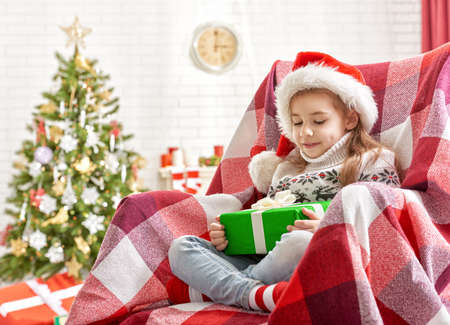 holiday house: Girl sitting in armchair with Christmas gift