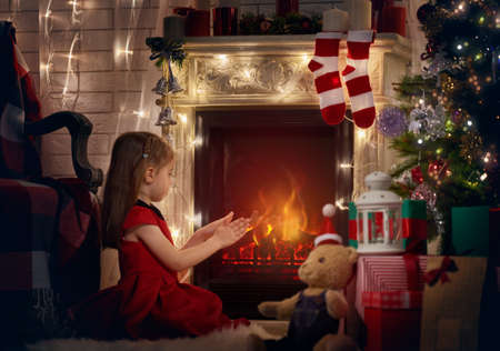 warms: Girl warms her hands by the fireplace. Stock Photo