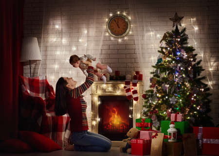 baby near christmas tree: mother with her baby playing near Christmas tree Stock Photo