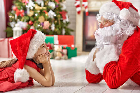 claus: Santa Claus and cute girl getting ready for Christmas. Stock Photo