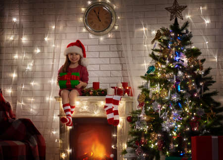holiday house: Little girl in Santas hat sitting on the fireplace and holding a gift in hands