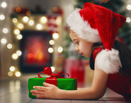 red hat: Funny child in Santa red hat holding Christmas gift in hand.
