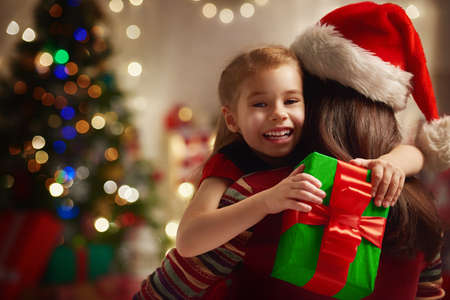relationship love: Mother and daughter exchanging Christmas gifts