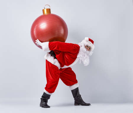 christmas funny: Portrait of funny Santa Claus with huge Christmas bauble.