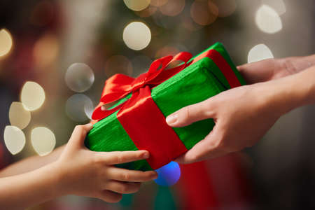 diciembre: Manos de los padres dando un regalo de Navidad para los niños.