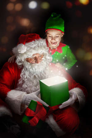 christmas gift box: Cute little girl and Santa Claus opening a magic gift box. Stock Photo