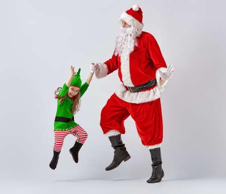 duendes de navidad: Santa and elf having fun and dancing. Foto de archivo
