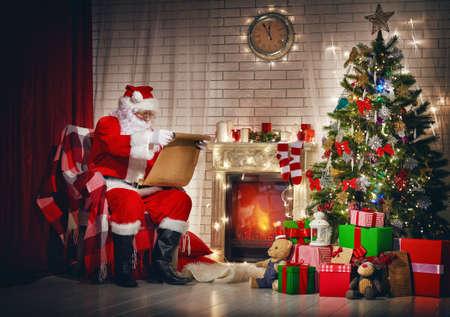 Portret van de zitting van de Kerstman in zijn kamer in het huis in de buurt van de kerstboom