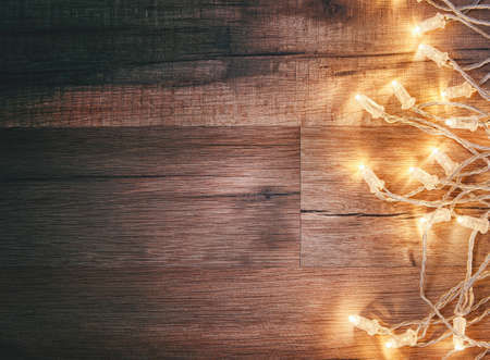 christmas lights background: Christmas garland lights on wooden rustic background.
