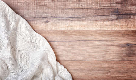 blanket: white knitted blanket on wooden background