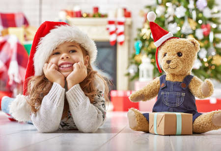 cute teddy bear: girl in Santa hat playing with teddy