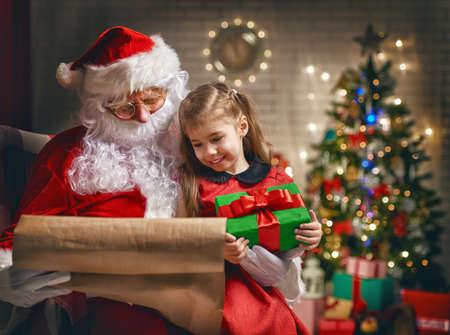 little colours: Santa Claus giving a present to a little cute girl