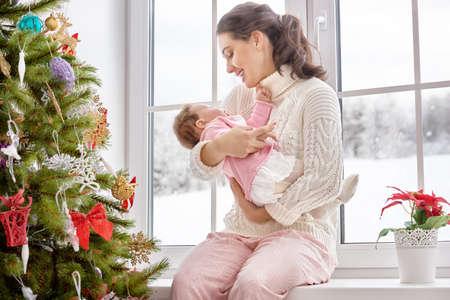 madre y bebe: Familia alegre feliz. Madre y bebé que abraza cerca de la ventana. Foto de archivo