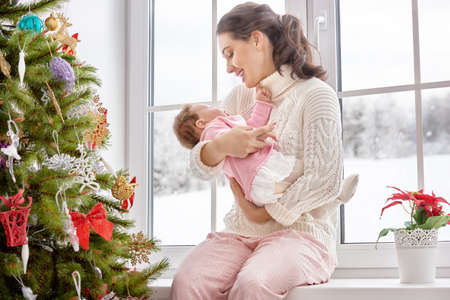 cute little girl smiling: Happy cheerful family. Mother and baby hugging near window. Stock Photo