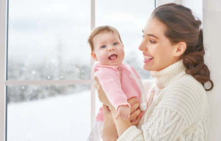 cheerful: Happy cheerful family. Mother and baby hugging near window. Stock Photo