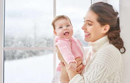 poblíž: Veselá rodina. Matka a dítě objímání poblíž okna.