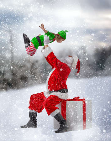 elf: Jolly elf and Santa Claus play together. Stock Photo