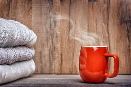 stack of clothes from knitted and cup of drink on a wooden background Stockfoto