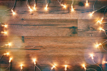 Christmas garland lights on wooden rustic background.