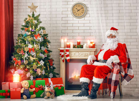 candle lights: Portrait of Santa Claus sitting at his room at home near Christmas tree