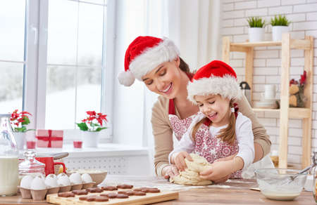 mother and daughter cooking Christmas biscuits Imagens - 47723618