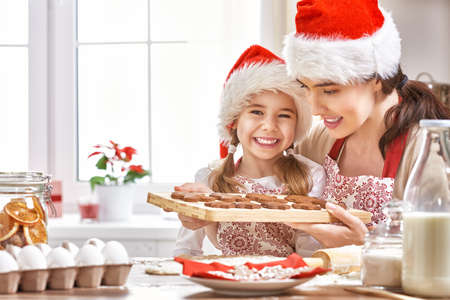 mother and daughter cooking Christmas biscuits