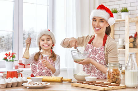 christmas morning: mother and daughter cooking Christmas biscuits