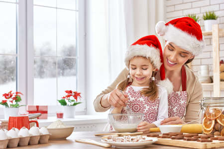 holiday decor: mother and daughter cooking Christmas biscuits