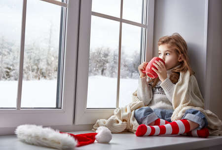 cold: little girl sitting by the window with a cup of hot drink and looking at the winter forest