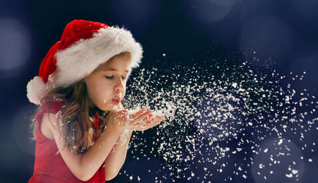 christmas fun: winter time! Happy little girl blowing on snow