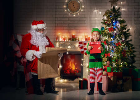 miracle tree: Santa and an elf getting ready for Christmas. Stock Photo