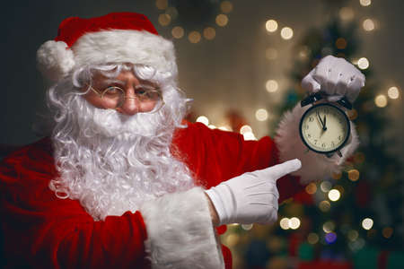 happy holidays: Portrait of Santa Claus with alarm clock in hand