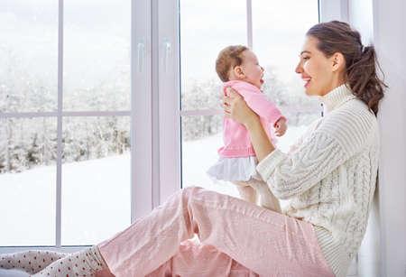 felicidade: Família alegre feliz. Mãe e bebê abraçando perto de uma janela.