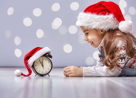 christmas concept: Christmas Eve! Cheerful child in a Christmas hat with alarm clock Stock Photo