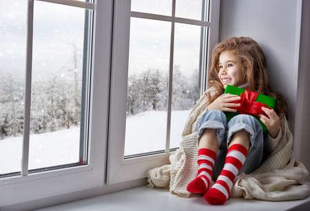 小さな女の子のギフトとウィンドウに座って、冬の森を見て 写真素材